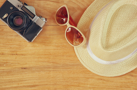 fedora hat: top view of stylish hat woman sunglasses old camera  wooden table. vaction and travel concept