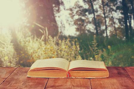 libro abierto: libro abierto sobre la mesa rústica de madera en frente de paisaje salvaje y la puesta del sol explosión de la luz