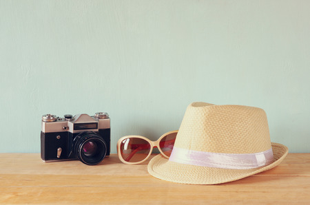fedora hat: fedora hat sunglasses old vintage camera over wooden table. relaxation or vacation concept