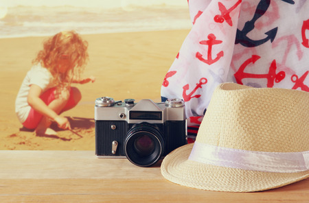fedora: fedora hat old vintage camera and scarf over wooden table and sea landscape background. relaxation or vacation concept