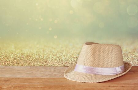 fedora: Fedora hat over wooden table and glitter background
