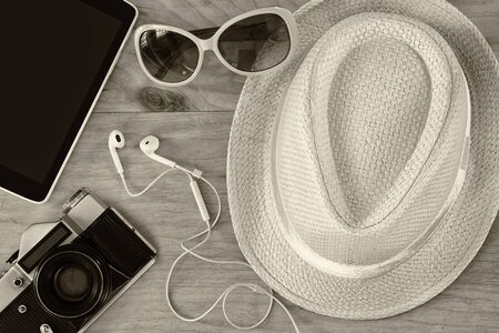top view of stylish hat woman sunglasses old camera and tablet device over wooden table. black and white photo. vaction and travel concept Stock Photo