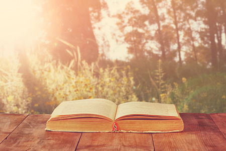 open book over wooden rustic table in front of wild landscape and sunset light burst