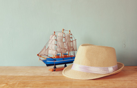 fedora: fedora hat and wooden boat over wooden table and blue background. relaxation or vacation concept