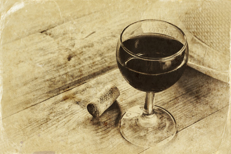 red wine glass on wooden table. vintage filtered image. black and white style photo