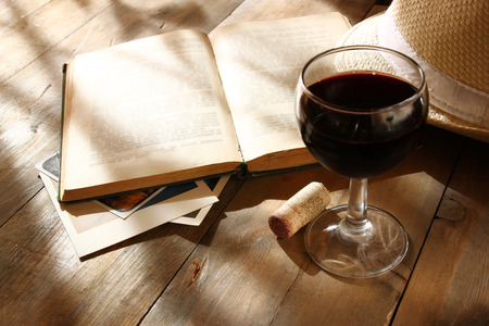 red wine glass and old book on wooden table at sunset burst. vintage filtered image