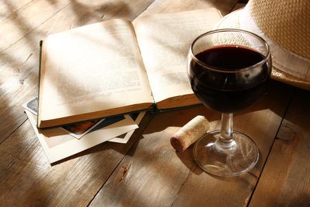 Ly rượu vang đỏ và sách cũ trên bàn bằng gỗ vào lúc hoàng hôn bùng nổ. Hình ảnh được lọc cổ điển