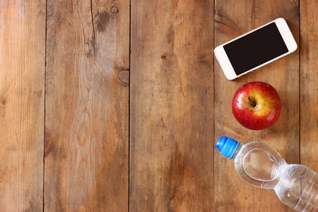 fitness concept with bottle of water mobile phone and apple over wooden background. filtered image