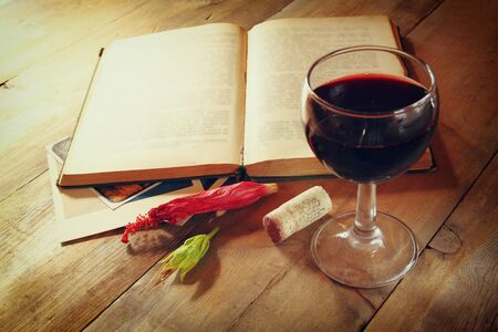 Red wine glass and old open book on wooden table at sunset burst. vintage filtered image photo