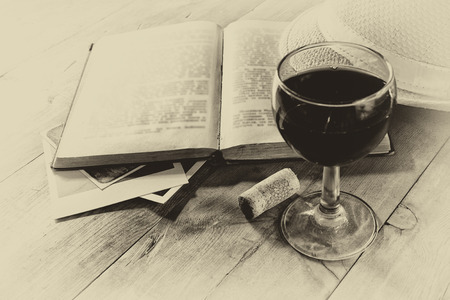 red wine glass on wooden table. vintage filtered image. black and white style photo photo