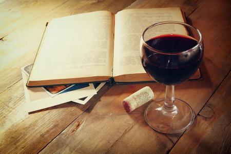 赤ワインのガラス、サンセット バーストで木製のテーブル上の古いオープン本。ビンテージのフィルターされたイメージ