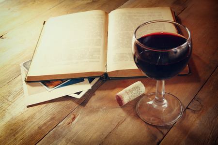 Red wine glass and old open book on wooden table at sunset burst. vintage filtered image
