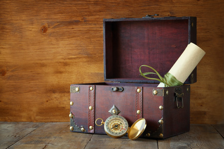 treasure box: Antique compass on wooden table Stock Photo