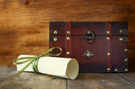 old papers: Antique wooden chest with old parchment on wooden table