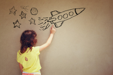 imagination: back view of cute kid girl imagine space rocket with set of infographics over textured wall background