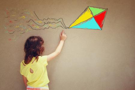 niños pintando: Foto de chico lindo imaginar vuelo de la cometa. conjunto de infografías sobre el fondo de la pared con textura Foto de archivo