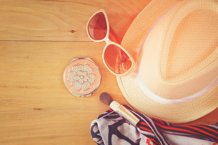 miror: top view photo of woman accessories  different objects on wooden background. instagram style filtered image
