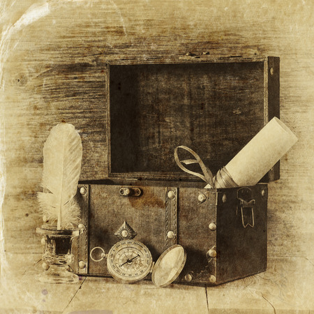 Antique compass inkwell and old wooden chest on wooden table.  black and white style old photo