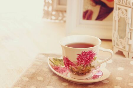 woman drinking tea: Black tea in elegant vintage porcelan cup on wooden table