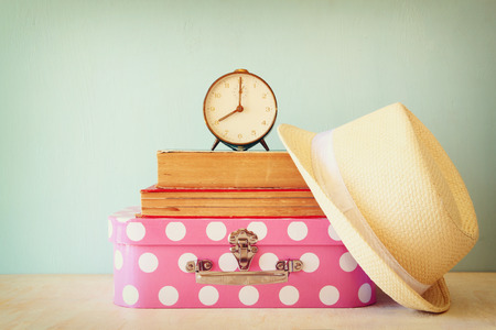 pink hat: stack of old suitcase books and vintage clock over wooden table. retro style image Stock Photo