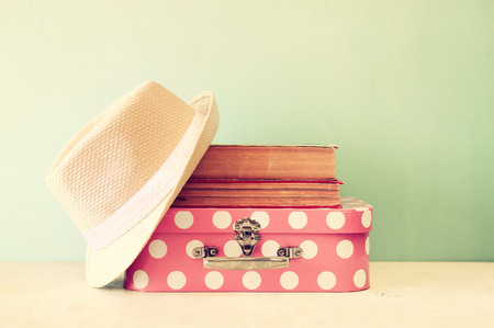 photo of pink suitcase with polka dots fedora hat and stack of books over wooden table retro style image