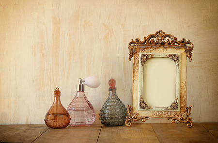 fragrance: image of victorian vintage antique classical frame and perfume bottles on wooden table. filtered image