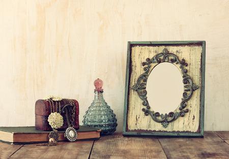 木製のテーブルにビクトリア朝ヴィンテージ アンティーク クラシック フレーム ジュエリー、香水のボトルのイメージ。フィルターされたイメージ