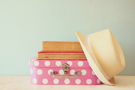 fedora: photo of pink suitcase with polka dots fedora hat and stack of books over wooden table retro style image