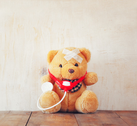 sick teddy bear: Teddy Bear with Bandage  and  stethoscope over wooden background