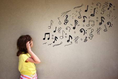 schattige meisje luistert naar muziek notities naast gestructureerde achtergrond