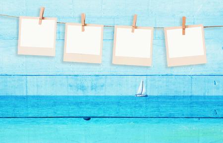 oude polaroid foto frames hnaging op een touw het dubbele belichting van de zeilboot met aan de horizon op de zee en houten planken achtergrond