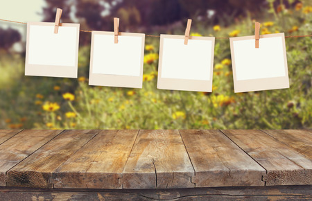 old polaroid photo frames hnaging on a rope with vintage wooden board table in front of summer flowers field bloom landscape photo