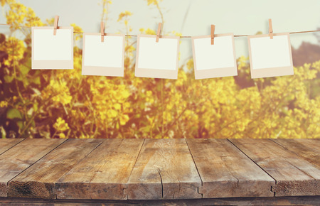 old photo frames hnaging on a rope with vintage wooden board table in front of summer flowers field bloom landscape photo