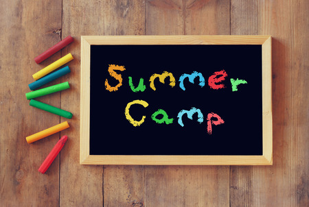 top view of blackboard with the phrase summer camp written on it and colorful crayons over wooden background