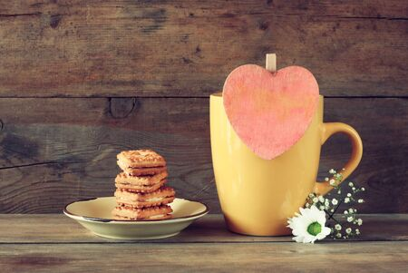 mag: yellow mag with a wooden vintage pink heart and cookies on the plate on wooden table