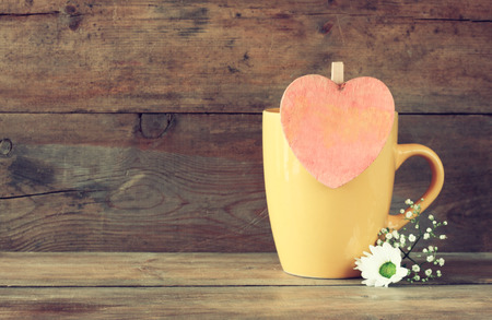 mag: yellow mag with a wooden vintage pink heart on wooden table Stock Photo