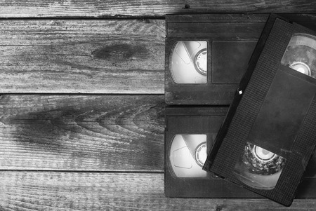 video cassette tape: stack of video tape cassette over wooden background. top view black and white photo Stock Photo
