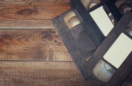 stack of video tape cassette over wooden background. top view photo