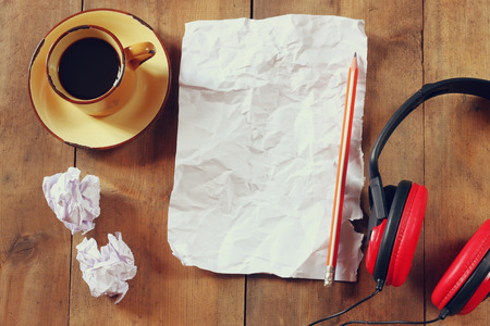 writers block: top view image of crumpled paper next to headphones and cup of coffee over wooden table