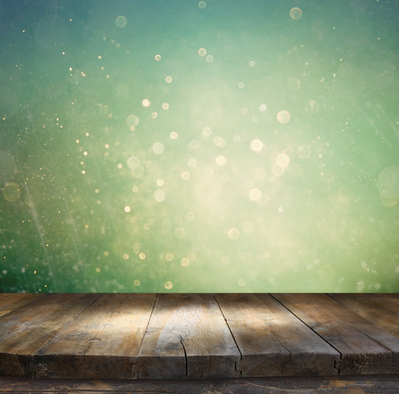 country christmas: rustic wood table in front of glitter silver blue and gold bokeh lights