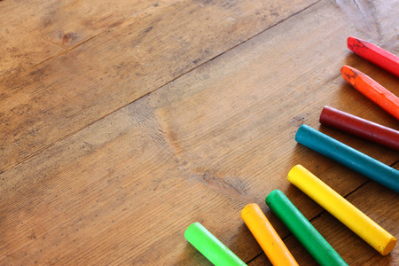 play of color: image of various colorful crayons on wooden table Stock Photo