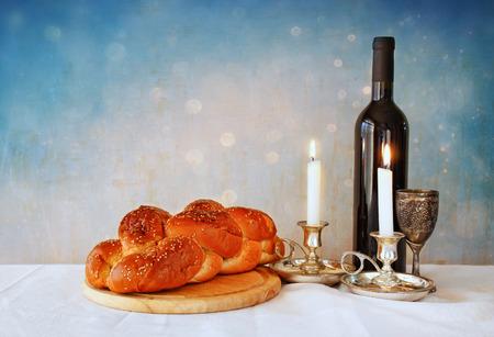 shabat: imagen shabbat. jalá pan vino shabbat y candelas en mesa de madera. brillo superposición