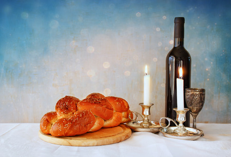 shabbat image. challah bread shabbat wine and candelas on wooden table. glitter overlay