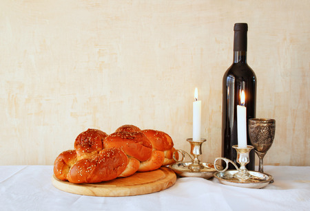 shabbat image. challah bread shabbat wine and candelas on wooden table. vintage filtered image photo
