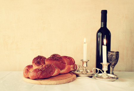 shabbat image. challah bread shabbat wine and candelas on wooden table. vintage filtered image Foto de archivo