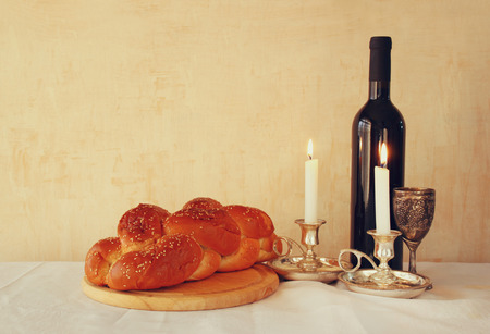 jewish: shabbat image. challah bread shabbat wine and candelas on wooden table. vintage filtered image Stock Photo