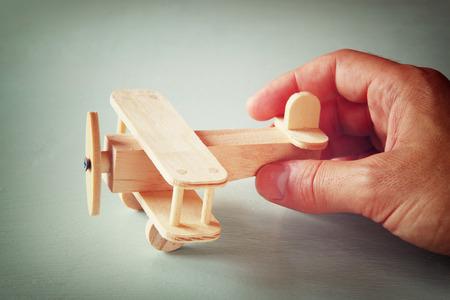 sencillez: cerca de la foto de la mano del hombre con el avión de juguete de madera sobre fondo de madera. filtrado de la imagen. la aspiración y la simplicidad concepto