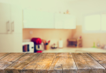 a kitchen: empty table board and defocused white retro kitchen background