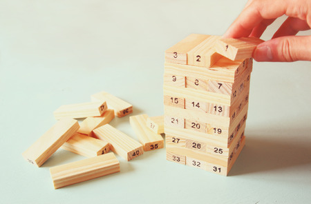 tower block: male hand placing wooden block on a tower. planing and strategy concept