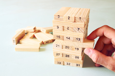 success risk: male hand placing wooden block on a tower. planing and strategy concept